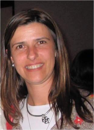 Foto da professora Cláudia Pinho Hartleben sorrindo. Ela é branca, cabelos lisos pela altura dos ombros, soltos..